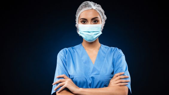 Serious doctor in medical mask and cap looking camera