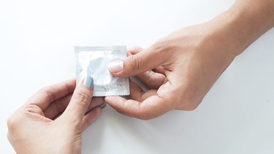 Condom in male hand and female hand, give condom safe sex concept on white background