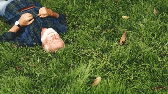 Elderly man sleeping on green grass