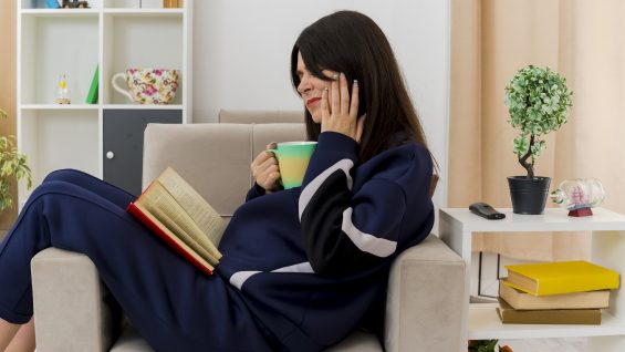 aching young pretty caucasian girl sitting on armchair in designed living room holding cup with book on legs putting hand on cheek suffering from toothache reading book