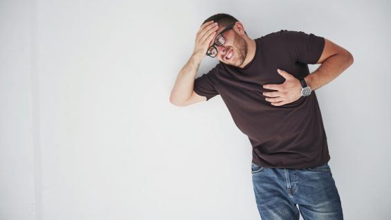 A young guy in casual clothes holds on to the heart and the head, it hurts or he is sick