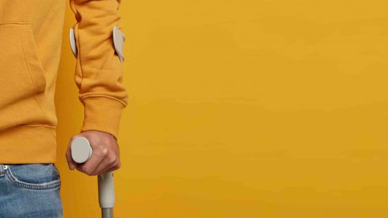 Human health care and injury concept. Unhappy bruised hurt man poses on crutches with frustrated expression, needs support after accident, stands against yellow wall, blank space for your text